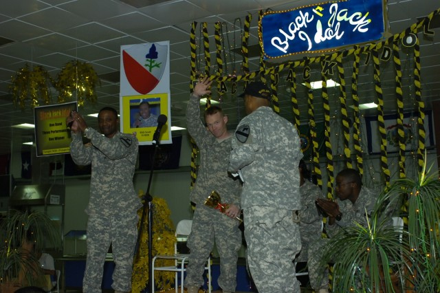 After accepting his trophy for winning the first-ever Black Jack Idol competition from the commander of the 2nd Brigade Combat Team, 1st Cavalry Division, Col. Bryan Roberts (right), Milwaukee native Pfc. Daniel Jens waves to the crowd.