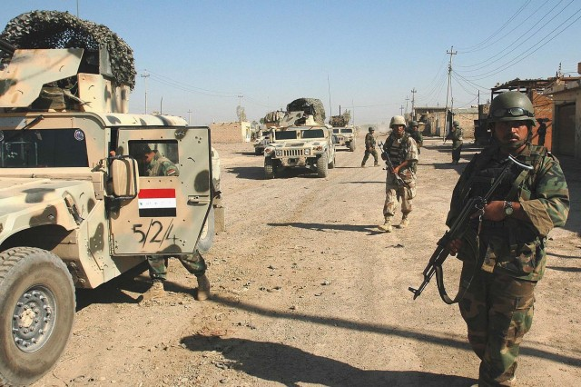 Operation Rock Wrench clears industrial section of Baqouba - 5th Iraqi Army Division soldiers secure a street before clearing the buildings in the industrial section of southern Baqouba during Operation Rock Wrench Sept 22.  Iraqi forces focused on clearing structures while U.S. forces provided security.