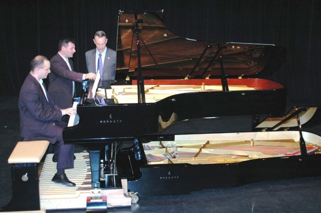 VICENZA, Italy - As concert pianist Marco Bruson (seated) plays, piano-maker Luigi Borgato (center) shows Col. Skip Davis, Southern European Task Force chief of staff, a feature of the Double Borgato concert grand piano that he built by hand. Borgato offered a free concert to military spouses at the Soldiers' Theatre here Sept. 26 as part of activities held in the Vicenza American military community to recognize the contributions military spouses make to their families and to the nation