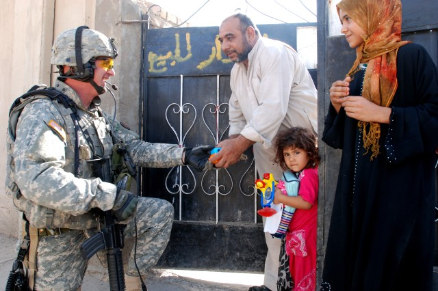 Multi-National Corps - Iraq Command Sgt. Maj. Neil Ciotola distributes toys to a family in Baghdad's Hurriyah neighborhood Sept. 20.