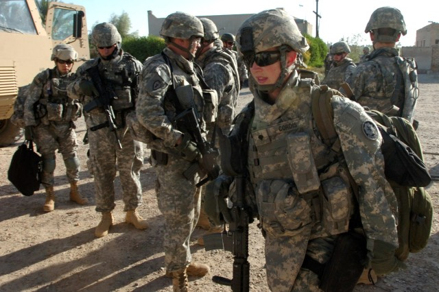 Spc. Kari Cordis, a medic for the Fires Squadron, 2nd Stryker Cavalry Regiment, who hails from Terre Bonne, Ore. walks past her fellow Fires Squadron Soldiers into a school that will be set up as a make-shift healthcare clinic during a combined medical effort in Bassam, Iraq Sept. 27.