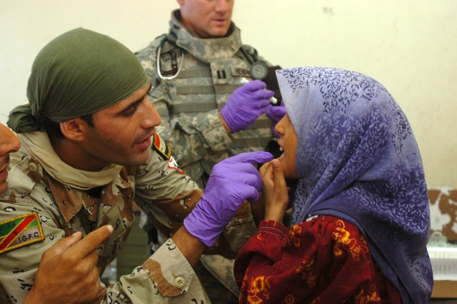 Iraqi Army Pvt. Ahmed Abdualsuda, a medic with the 2nd Brigade, 9th Iraqi Army Division (Mechanized) examines a little girl's mouth which is causing her pain at a school set up as a make-shift clinic during a combined medical effort near Bassam, Iraq Sept. 27.