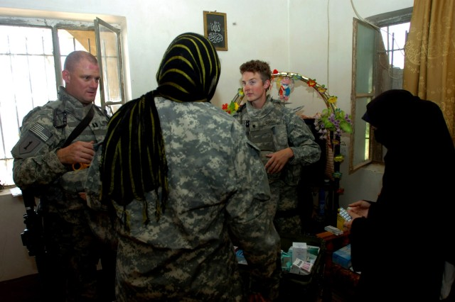 Through an Iraqi interpreter (center), Austin, Ind. native Capt. John Hendricks (left), squadron surgeon, and Spc. Kari Cordis, a medic, who hails from Terre Bonne, Ore. assist an Iraqi woman (right) by explaining to her the proper dosage of medication to take for a cold during a combined medical effort near Bassam, Iraq Sept. 27.