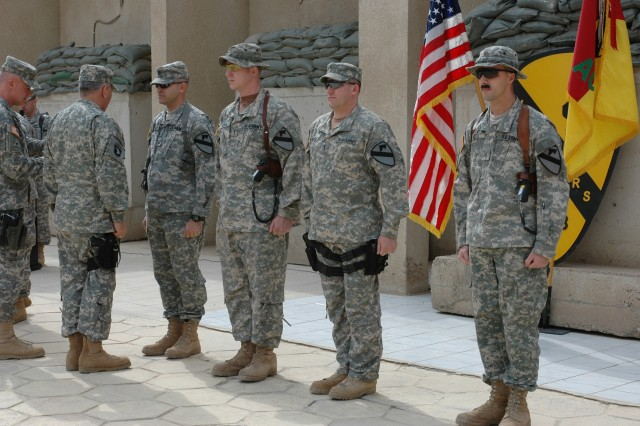Col. Dan Shanahan, commander of 1st Air Cavalry Brigade, 1st Cavalry Division, (far left) and Gen. Richard A. Cody, (second from left) present the Air Medal with Valor to, from left to right, Capt. Matthew Carlsen, chief warrant officers 3 Christopher Ezell and Les McNellie and Chief Warrant Officer 2 Rich Reid. Carlsen, Ezell, McNellie and Reid received their valor awards for assisting a ground unit that had come under small arms fire and grenade attacks in December.