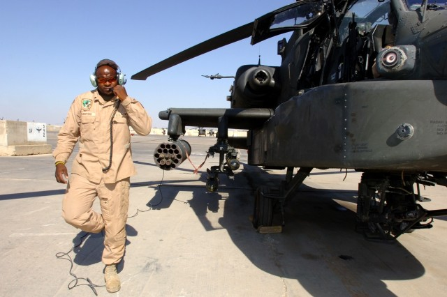 """Topeka, Kan., native Spc. Anthony Crawford, an Apache crew chief for Company C, 1st """"Attack"""" Battalion, 227th Aviation Regiment, 1st Air Cavalry Brigade, 1st Cavalry Division, walks around the aircraft to make some final inspections before he helps it taxi for take off at Camp Taji, Iraq, Sept. 27. Unlike a car, the Apache has no rear mirrors, the pilots depend on the eyes of the crew chief while backing out of their parking spot."""