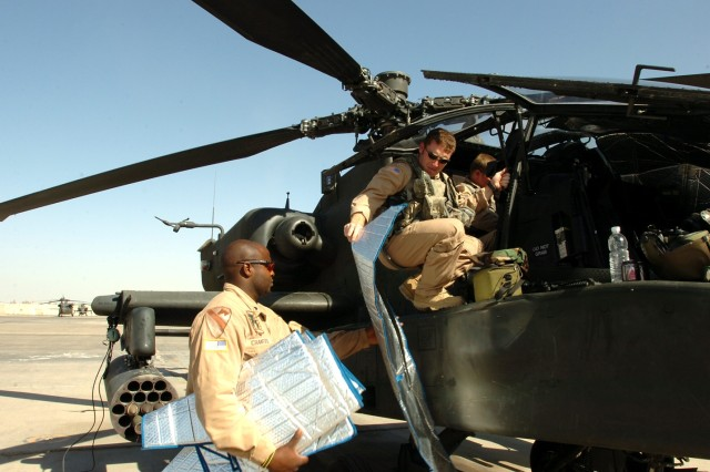 """Deming, N.M., native Joshua Robertson (right), an AH-64D Apache attack helicopter pilot for Company C, 1st """"Attack"""" Battalion, 227th Aviation Regiment, 1st Air Cavalry Brigade, 1st Cavalry Division, hands down a sun visor to Topeka, Kan., native Spc. Anthony Crawford (left), an Apache crew chief for Co. C, 1-227th, as they ready the aircraft for flight at Camp Taji, Iraq, Sept. 27."""