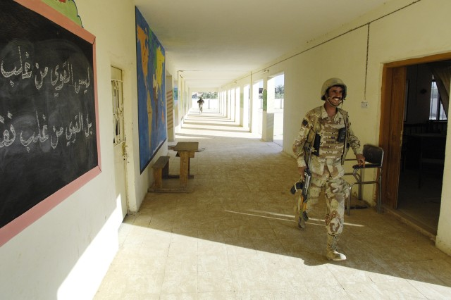 An Iraqi soldier appears to be enjoying the patrol as he walks through a school.