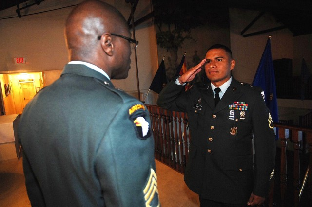 Sponsor Sgt. lst Class Akida Maxwell looks over the uniform of contestant, Staff Sgt. Jorge Toro, as he salutes in prepartation for his Noncommissioned Officer of the Year board appearance Oct. 1, 2007.