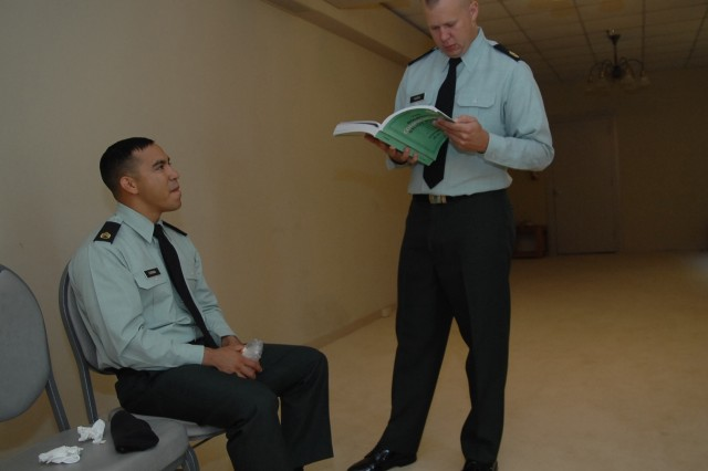 Sponsor Sgt. lst Class Jason Harris goes over last-minute notes with contestant, Staff Sgt. David Corona, just before his Noncommissioned Officer of the Year board appearance on the first day of the Best Warrior Competition Oct. 1, 2007.