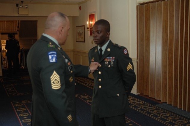 Sponsor, Command Sgt. Maj. Luis Lopez, makes adjustments to the uniform of contestant Sgt. Sadat Allhassan just before Allhassan's board appearance during the 2007 Noncommissioned Officer of the Year competition Oct. 1 at Fort Lee, Va.