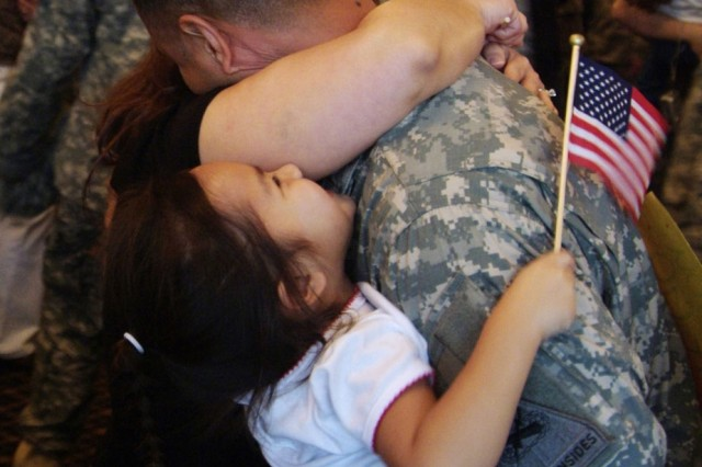 A Soldier hugs his Family at Giessen Army Depot, Germany, following his 14-month tour in Iraq. At a recent Deployment-Related Community Counseling Conference in Europe, participants discussed the Battlemind Training System, which prepares Families for reunion and reintegration.