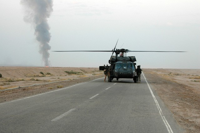 """A UH-60 Black Hawk from the 3rd """"Spearhead"""" Battalion, 227th Aviation Regiment, 1st Air Cavalry Brigade, 1st Cavalry Division, lands during an aerial gunnery while the door gunners switch positions, Sept. 30. In the background a target burns after the previous crew shot it with precision fire."""