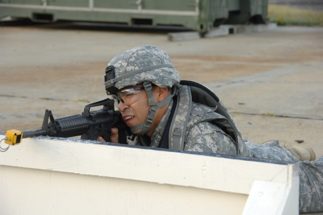 "Competitor Staff Sgt. David Corona negotiates a barricade as part of a reflexive fire exercise during the 2007 Noncommissioned Officer/Soldier of the Year competition Oct. 2 at Fort Lee, Va. The exercise prepares the Soldier for an upcoming ""urban warfare"" range event."