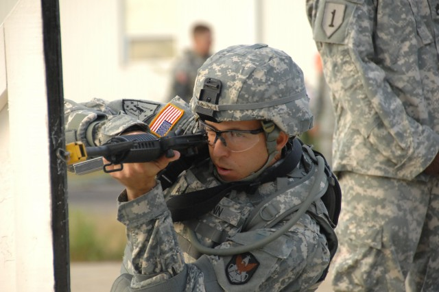 """Competitor Sgt. Patrick Mann negotiates a barricade as part of a reflexive fire exercise during the 2007 Noncommissioned Officer/Soldier of the Year competition Oct. 2 at Fort Lee, Va. The exercise prepares the Soldier for an upcoming """"urban warfare"""" range event."""
