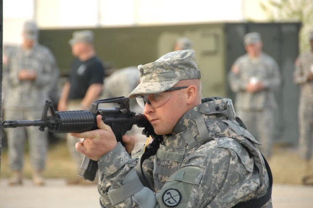 "Competitor Spc. Erik Nowak negotiates a barricade as part of a reflexive fire exercise during the 2007 Noncommissioned Officer/Soldier of the Year competition Oct. 2 at Fort Lee, Va. The exercise prepares the Soldier for an upcoming ""urban warfare"" range event."