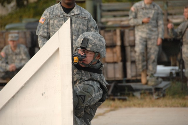"""Competitor Staff Sgt. Travis Snook negotiates a barricade as part of a reflexive fire exercise during the 2007 Noncommissioned Officer/Soldier of the Year competition Oct. 2 at Fort Lee, Va. The exercise prepares the Soldier for an upcoming """"urban warfare"""" range event."""