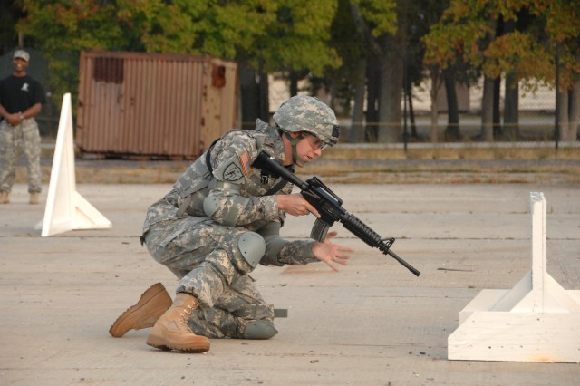 """Competitor Staff Sgt. Brian Yoder negotiates a barricade as part of a reflexive fire exercise during the 2007 Noncommissioned Officer/Soldier of the Year competition Oct. 2 at Fort Lee, Va. The exercise prepares the Soldier for an upcoming """"urban warfare"""" range event."""
