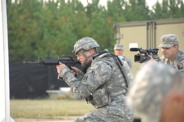 """Competitor Sgt. Nicholas Johnson negotiates a barricade as part of a reflexive fire exercise during the 2007 Noncommissioned Officer/Soldier of the Year competition Oct. 2 at Fort Lee, Va. The exercise prepares the Soldier for an upcoming """"urban warfare"""" range event."""