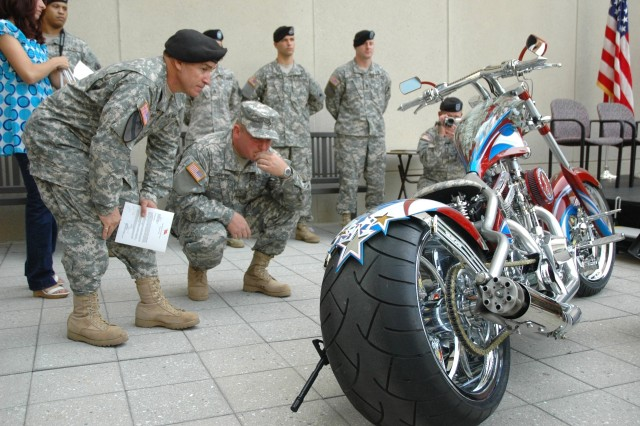 "Chief Warrant Officer 3 David Vasquez and Pfc. Joseph Scheibe admire the ""Patriot Chopper"" following its Sept. 27 unveiling at the Army National Guard Readiness Center in Arlington, Va. The two were among four Guard Soldiers whose ideas were incorporated into the design by TV's Orange County Choppers."