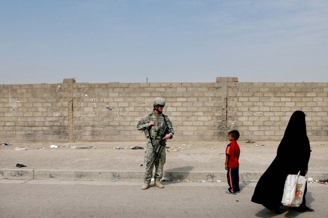 A Soldier with Company A, 1st Battalion, 149th Infantry Regiment talks with a local Iraqi child during a routine presence patrol through the Al Furat section of Baghdad.