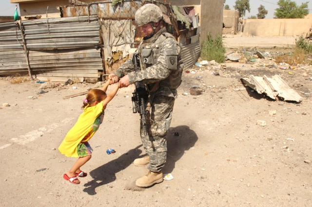 Spc. Derrick Watkins, an infantryman with Company A, 1st Battalion, 149th Infantry Regiment, plays with a local Iraqi child while on patrol in the Al Furat section of Baghdad.
