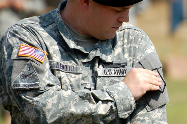 Capt. Lawrence Devoto, an intelligence officer with the 1st Combat Support Brigade (Maneuver Enhancement), places the new unit patch on his uniform during an Oct. 2 ceremony.