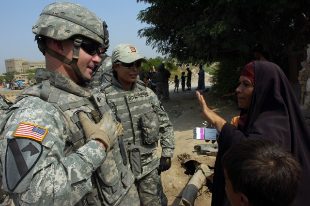 """Lt. Col. Michael Tarsa, commander of the 3rd Battalion, 82nd Field Artillery Regiment """"Red Dragons,"""" 2nd Brigade Combat Team, 1st Cavalry Division, talks with a woman about the medical treatment she received during a cooperative medical engagement in central Baghdad's Qadisiyah neighborhood Oct. 1."""