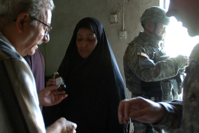 Dr. Asim Izzat, an internist who works closely with the 2nd Brigade Combat Team, 1st Cavalry Division, and Staff Sgt. Jerry Normoyle, a Grove City, Ohio native with the 422nd Civil Affairs Battalion, give medicine dosing directions to an Iraqi woman during a cooperative medical engagement in central Baghdad Oct. 1.