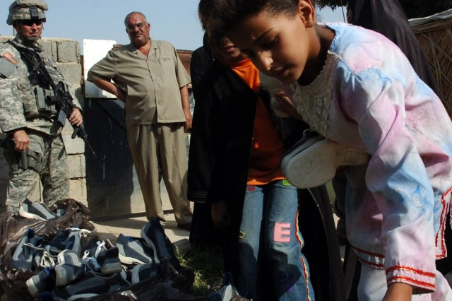 An Iraqi girl picks out a new pair of shoes during a cooperative medical engagement and humanitarian aid drop organized by Battery A, 3rd Battalion, 82nd Field Artillery Regiment, 2nd Brigade Combat Team, 1st Cavalry Division and the 422nd Civil Affairs Battalion team members attached to the battalion Oct. 1.