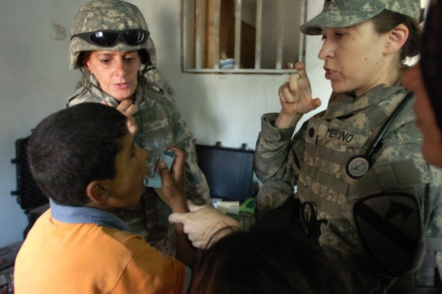 The surgeon for the 2nd Brigade Combat Team, 1st Cavalry Division, Buffalo, N.Y., native Lt. Col. Margret Merino (right), shows a young boy how to properly use his inhaler during a cooperative medical engagement in Baghdad's Qadisiyah neighborhood Oct. 1. Troops from the 3rd Battalion, 82nd Field Artillery Regiment and the 422nd Civil Affairs Battalion organized the event inside a camp in central Baghdad.