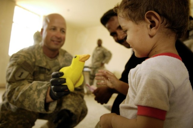Staff Sgt. Mark Plavan, a medic with Company C, 203rd Brigade Support Battalion, offers a toy to a patient during a combined medical operation in Hollandia, Iraq.