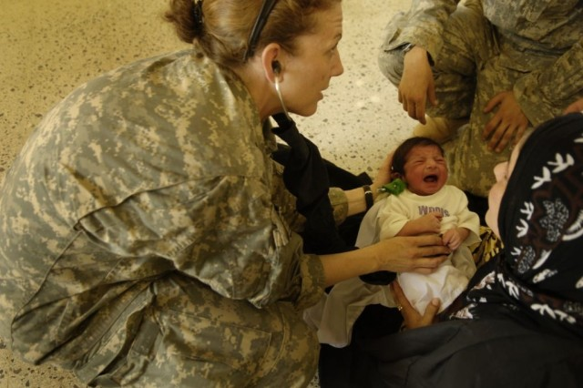 Maj. Cynthia Majerske, a 3rd Brigade Support Battalion surgeon attached to the 1st Cavalry Regiment, examines an Iraqi child during a combined medical operation in Hollandia, Iraq.