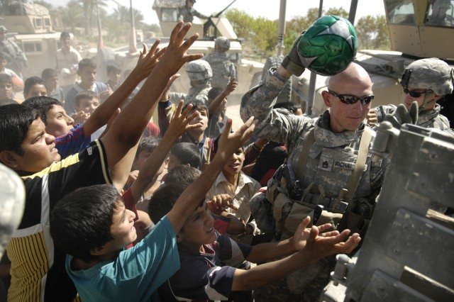 Sgt. 1st Class David Richardson and other Soldiers pass out soccer balls to eager children.