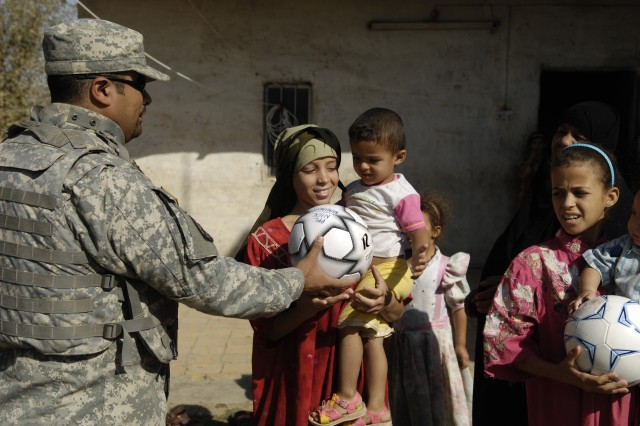 An interpreter assigned to the squadron helps pass out soccer balls.