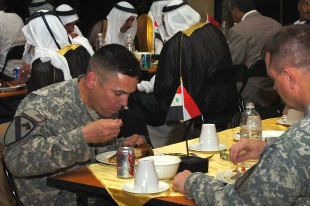 "Lt. Col. Kurt Pinkerton, commander, 2nd ""Lancer"" Battalion, 5th Cavalry Regiment, and Col. Paul E. Funk II, commander, 1st ""Ironhorse"" Brigade Combat Team, 1st Cavalry Division dine in the presence of Abu Ghraib tribal leaders and government officials during a dinner held at Camp Liberty, Iraq Oct. 1 to celebrate the success of recent reconciliation efforts within Abu Ghraib."