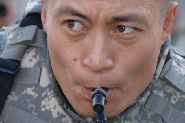 Competitor Spc. Heyz Seeker gets a drink from a hydration device during the Urban Warfare Orienteering Course event of the Department of the Army Best Warrior Competition at Fort Lee, Va., Oct. 1-5.
