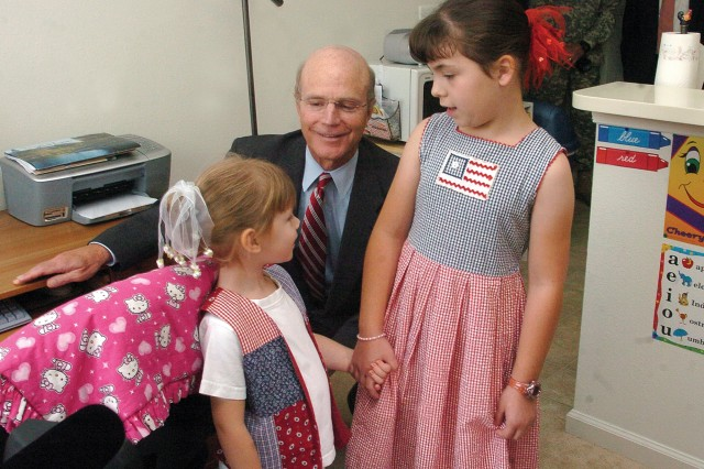 Annika Valliel and her sister, Naomi, talk with Secretary of the Army Pete Geren in their home Wednesday morning. Geren visited Fort Belvoir's George Washington Village.