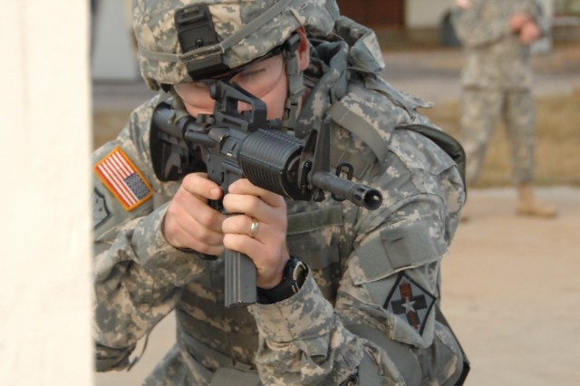 "Staff Sgt. Russell Burnham negotiates a barricade as part of a reflexive fire exercise during the 2007 Noncommissioned Officer/Soldier of the Year competition Oct. 2 at Fort Lee, Va. The exercise prepares the Soldier for an upcoming ""urban warfare"" range event."