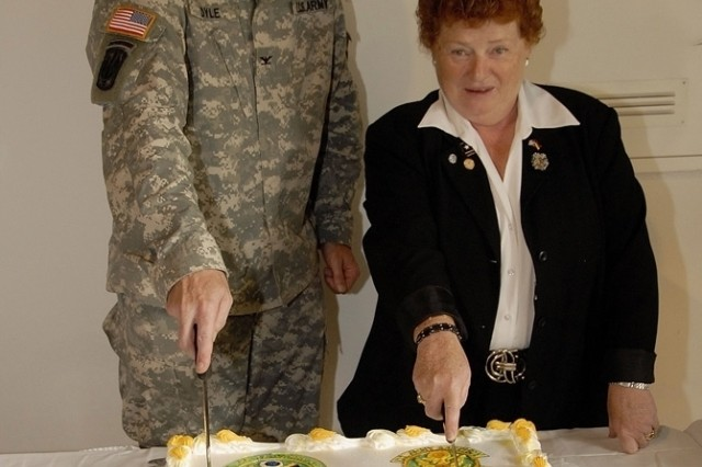 Col. Brian Boyle, commander of USAG Grafenwoehr, and Karin Santos, manager of USAG Garmisch, slice the cake during a transition of authority ceremony for Garmisch