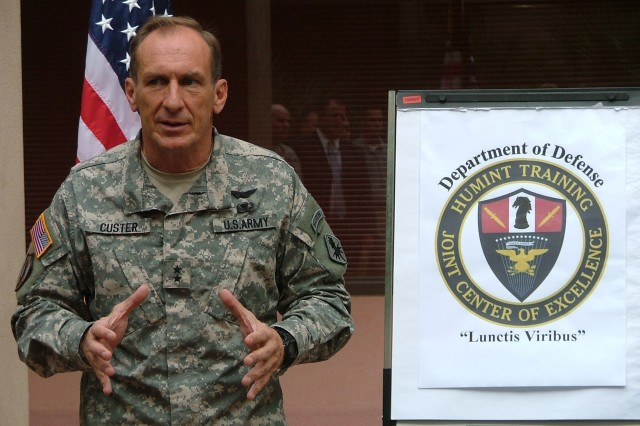 Maj. Gen. John Custer speaks to the crowd as the Human Intelligence Training-Joint Center of Excellence crest is revealed at a ceremony celebrating the center's completion Oct. 1 at Fort Huachuca, Ariz.