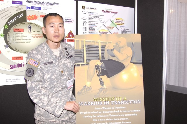 "Maj. Dan Ruecking of the Army Medical Action Plan shows the ""Warrior in Transition"" poster featuring Sgt. Maj. Brent Jurgensen who lost his leg in Iraq and remains on active duty."