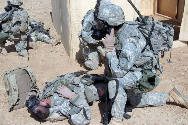 After assisting a role-playing injured Soldier with his mask, a Soldier calls for medical evacuation.