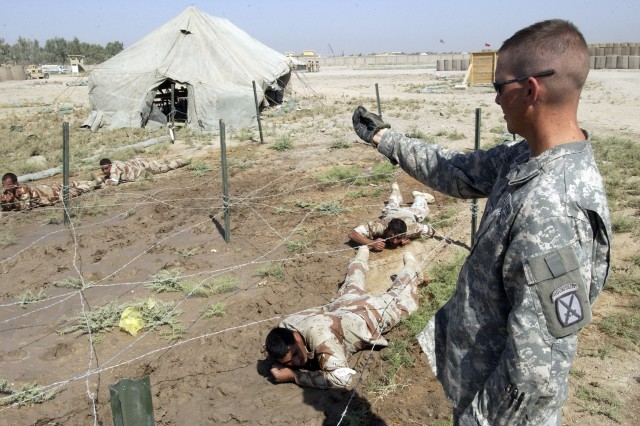 Staff Sgt. Charles Bruckner supervises trainees doing the low crawl.
