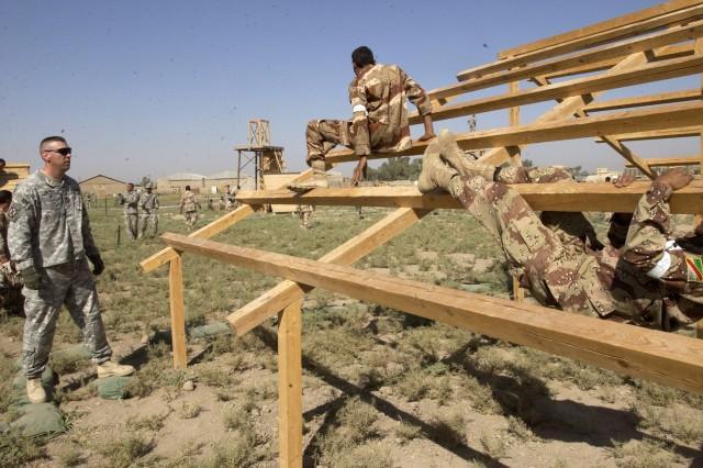 Sgt. 1st Class Carl Shipman watches trainees surmount an obstacle requiring strength and endurance.