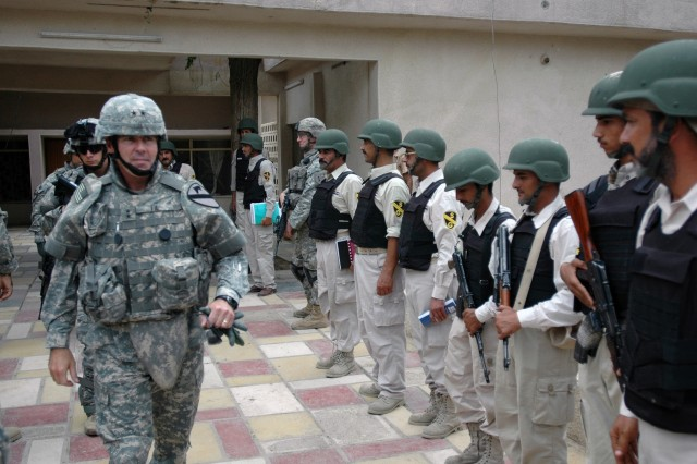 Maj. Gen. Joseph F. Fil Jr., commanding general of the Multi-National Division - Baghdad and the 1st Cavalry Division, departs a security coordination center in the southern Baghdad neighborhood of Saydiyah flanked by members of the local security volunteers Oct. 6.