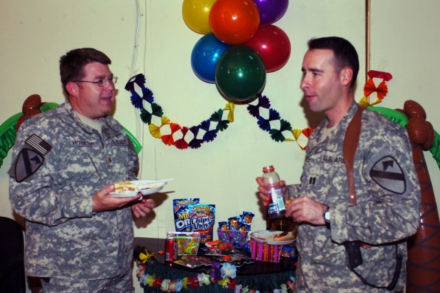 """St. Louis native Maj. Craig Hickerson (left), commander for the 1070th Psychological Operations Detachment, attached to the 1st """"Ironhorse"""" Brigade Combat Team, 1st Cavalry Division, discusses future plans upon returning home with Capt. Alejandro Restrepo, chief of operations for the 1st BCT during the Headquarters and Headquarters Troop's """"100 Days Left Party"""" at Camp Taji, Iraq Oct. 6.  HHT Soldiers celebrated the beginning of the end of their deployment after being extended three additional months."""