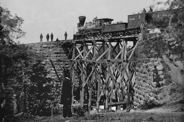 """The locomotive """"Firefly"""" stops on a trestle of the Orange and Alexandria Railroad in northern Virginia, captured by Union forces. The bridge was repaired under the direction of the famous Army engineer, Brig. Gen. Herman Haupt (standing in"""