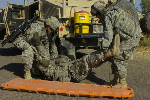"""Sgt. Franklin Sagun (left) and Spc. Paola Cossio prepare to move """"casualty,"""" Spc. Jude Wendel during a lane training exercise conducted by Soldiers from the 15th Brigade Support Battalion, 2nd Brigade Combat Team, 1st Cavalry Division, in Baghdad's International Zone Sept. 26."""