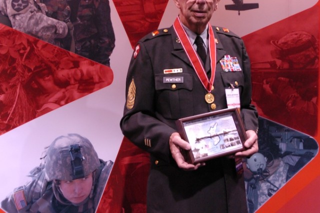 Command Sergeant Major (R) William Pewther holds a piece of wire from the Korean Demilitarized Zone in front of the 8th Army display at the Association of the United States Army convention October 8. Earlier in the day Pewther received the Sergeant Major of the Army William Bainbridge Medal for exceptional service to the noncommissioned officer corps during the opening ceremony for AUSA at the Washing D.C. convention center. Pewther served in the 7th Infantry Division in Pusan, Korea as part of 8th United States Army during the Korean War. 8th Army gave DMZ wire to Korean War veterans who visited the 8th Army display.