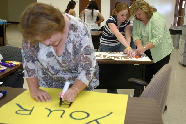Brinkley, Ark., native Renee Hicks (front) and Columbia, S.C., natives Beth Whitten (right) and Jenny Whitten (middle), make signs during a Family Readiness Group meeting Oct. 6 to be held up by waiting family members at the homecoming ceremonies for the Soldiers of the 15th Brigade Troops Battalion, 15th Sustainment Brigade, 1st Cavalry Division when they return to Fort Hood later this month from Iraq. The FRG also put together personalized baskets of snacks and hygiene items to place in the barracks rooms of single Soldiers when they return to Fort Hood.